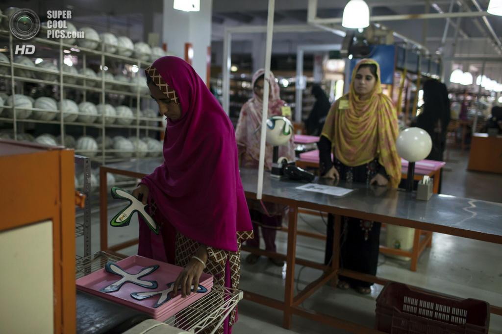 Пакистан. Сиялкот, Пенджаб. 16 мая. Работница фабрики вынимает фигурные панели из машины, которая наносит клей по краям. (REUTERS/Sara Farid)