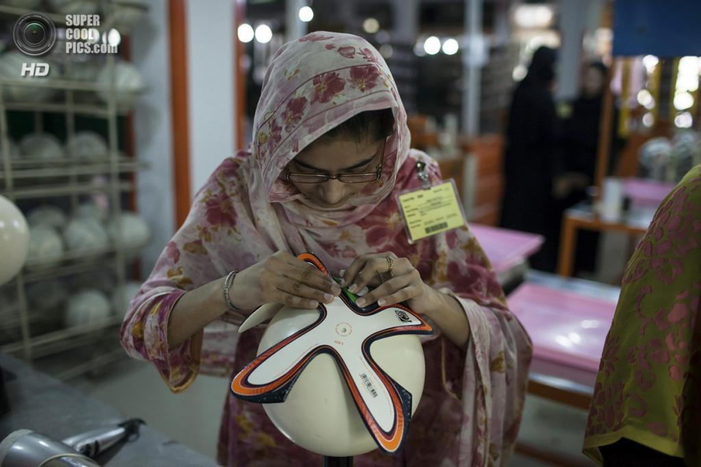 Пакистан. Сиялкот, Пенджаб. 16 мая. Работница фабрики оклеивает мяч фигурными панелями. (REUTERS/Sara Farid)