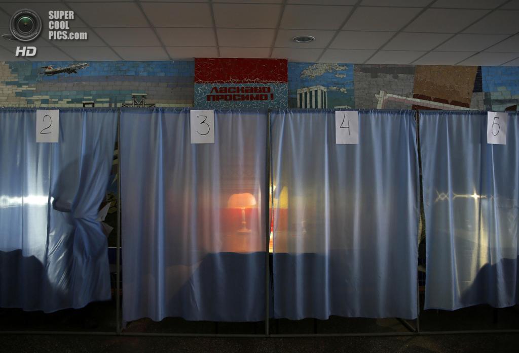 Украина. Красноармейск, Донецкая область. 25 мая. Мужчина выходит из кабинки для голосования. (REUTERS/Yannis Behrakis)