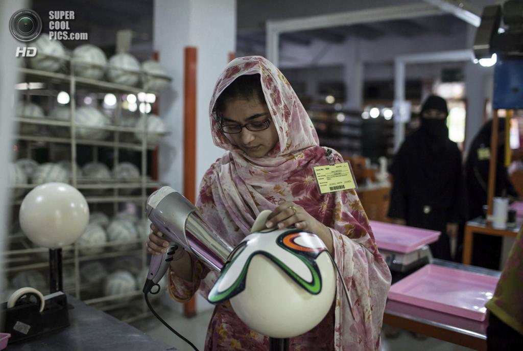 Пакистан. Сиялкот, Пенджаб. 16 мая. Работница фабрики использует фен для быстрого высушивания клея. (REUTERS/Sara Farid)