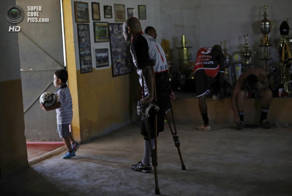 Бразилия. Сан-Паулу. 25 января. Алешандре Толеду с сынишкой готовится к выходу на поле. 4-летнего мальчика зовут Гу. (REUTERS/Nacho Doce)
