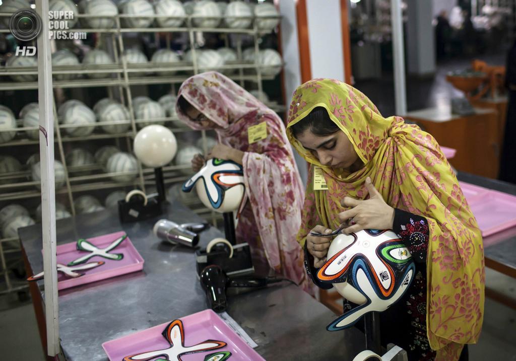 Пакистан. Сиялкот, Пенджаб. 16 мая. Работницы фабрики оклеивают мячи фигурными панелями. (REUTERS/Sara Farid)