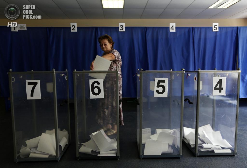 Украина. Красноармейск, Донецкая область. 25 мая. Женщина бросает бюллетени в урну для голосования. (REUTERS/Yannis Behrakis)
