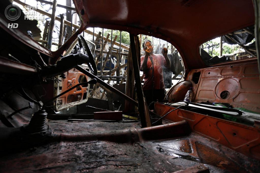 Индия. Калькутта, Западная Бенгалия. 26 мая. Hindustan Ambassador проходит ремонт в местной автомастерской. (AP Photo/Bikas Das)