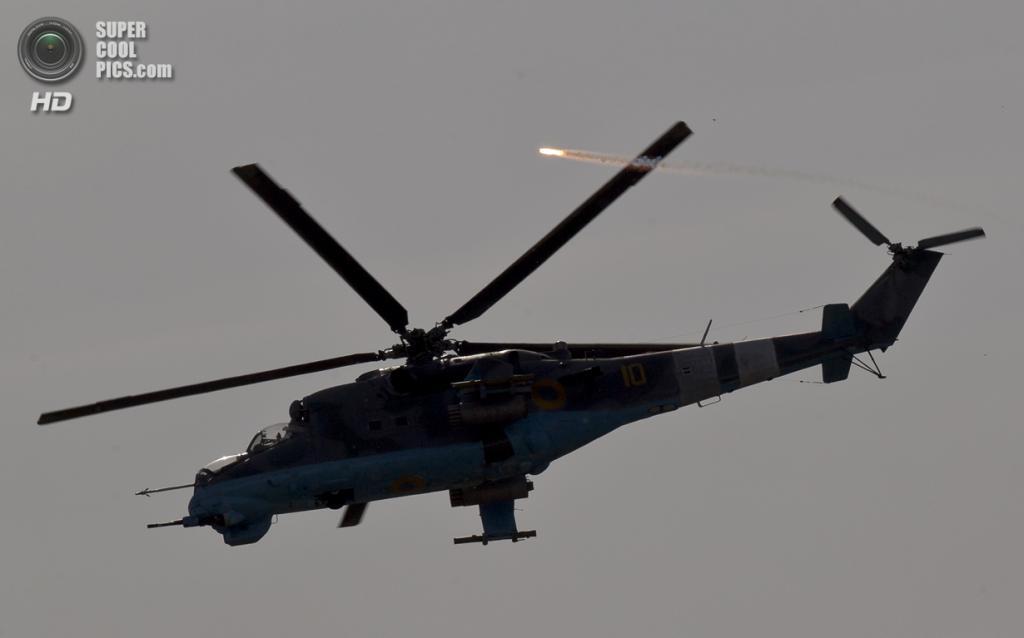 Украина. Донецк. 26 мая. Военный вертолёт Ми-24 отстреливает тепловые ловушки перед нанесением огневого удара. (REUTERS/Yannis Behrakis)