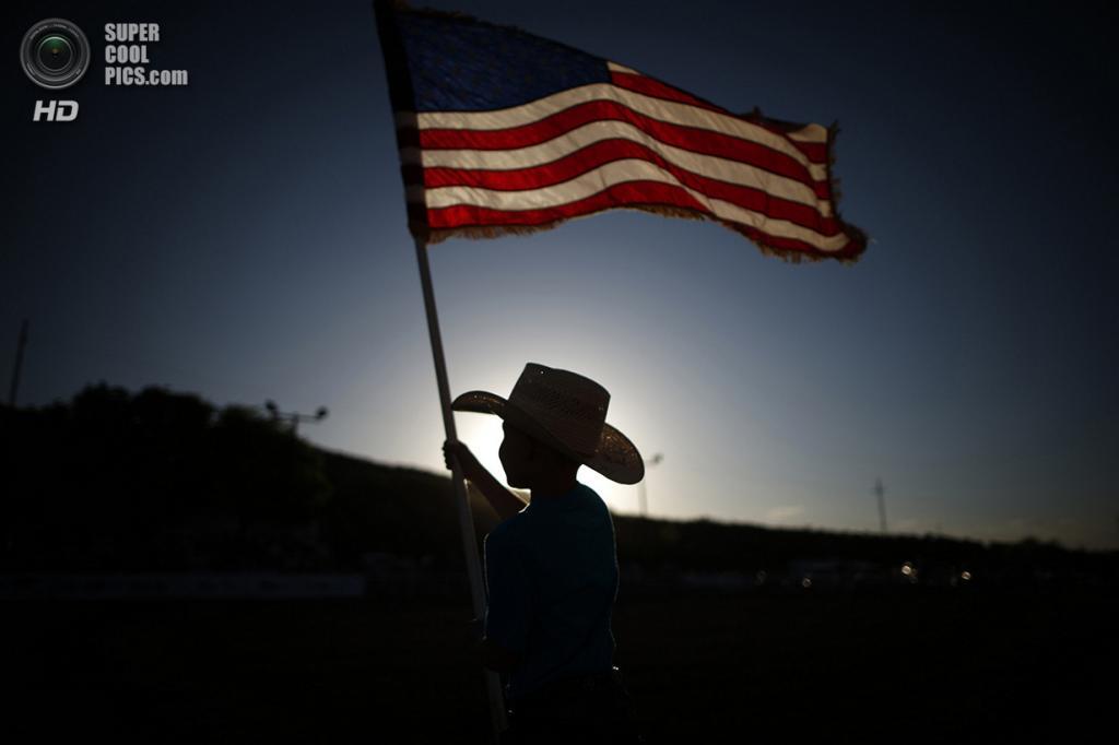 США. Трут-ор-Консекуэнсес, Нью-Мексико. 3 мая. 7-летний Эстебан Эдвардс машет национальным флагом США. (REUTERS/Lucy Nicholson)