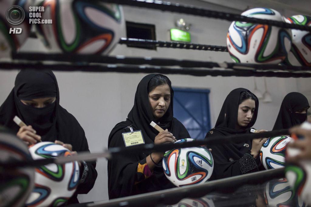 Пакистан. Сиялкот, Пенджаб. 16 мая. Работницы фабрики устраняют полости в швах. (REUTERS/Sara Farid)
