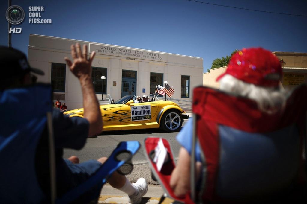 США. Трут-ор-Консекуэнсес, Нью-Мексико. 3 мая. Зрители парада приветствуют проезжающий автомобиль во время ежегодной «Фиесты». (REUTERS/Lucy Nicholson)