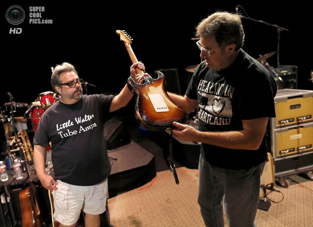США. Меса, Аризона. Легенда кантри Винс Гилл берёт у звукотехника Винни Гарсии свою гитару Fender Stratocaster 1957 года выпуска. Гарсия продал Гиллу эту гитару всего за $200 и пару ковбойских ботинок. (AP Photo/Matt York)