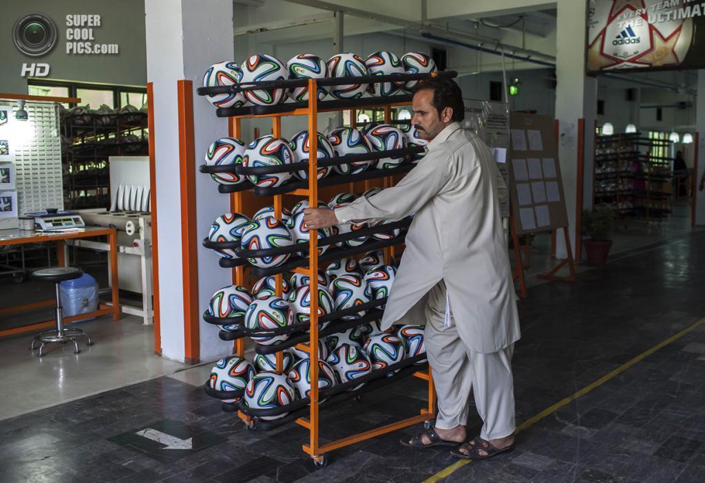 Пакистан. Сиялкот, Пенджаб. 16 мая. Работник фабрики увозит готовые мячи из цеха. (REUTERS/Sara Farid)
