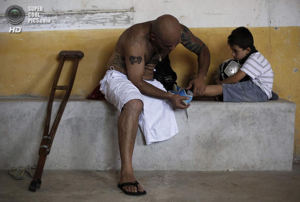 Бразилия. Сан-Паулу. 25 января. Алешандре Толеду снимает бутсы с ног сына после тренировки. (REUTERS/Nacho Doce)