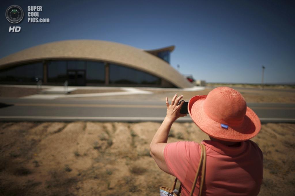 США. Трут-ор-Консекуэнсес, Нью-Мексико. 2 мая. Турист фотографирует Центр управления космопорта. (REUTERS/Lucy Nicholson)