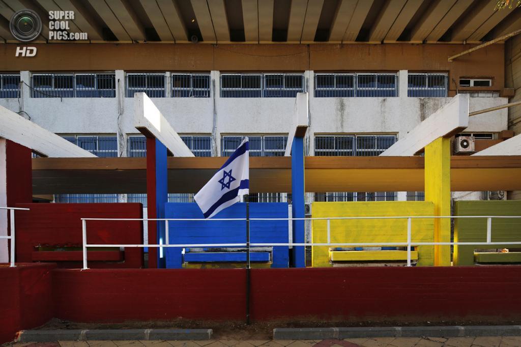 Израиль. Сдерот, Южный округ. 28 марта. Национальный флаг Израиля, развевающийся на школьном дворе. (REUTERS/Finbarr O'Reilly)
