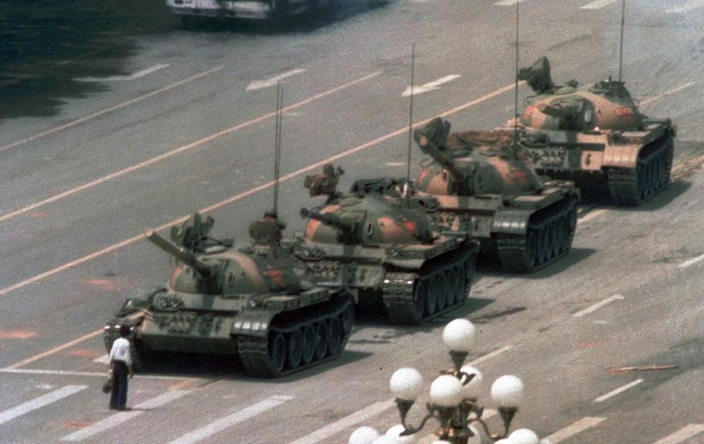 Китай. Пекин. 5 июня 1989 года. «Неизвестный бунтарь» — мужчина, в течение получаса сдерживавший колонну танков на площади Тяньаньмэнь. Вскоре его увели, а танки продолжили свой путь по бульвару Цаньгань. (AP Photo/Jeff Widener)