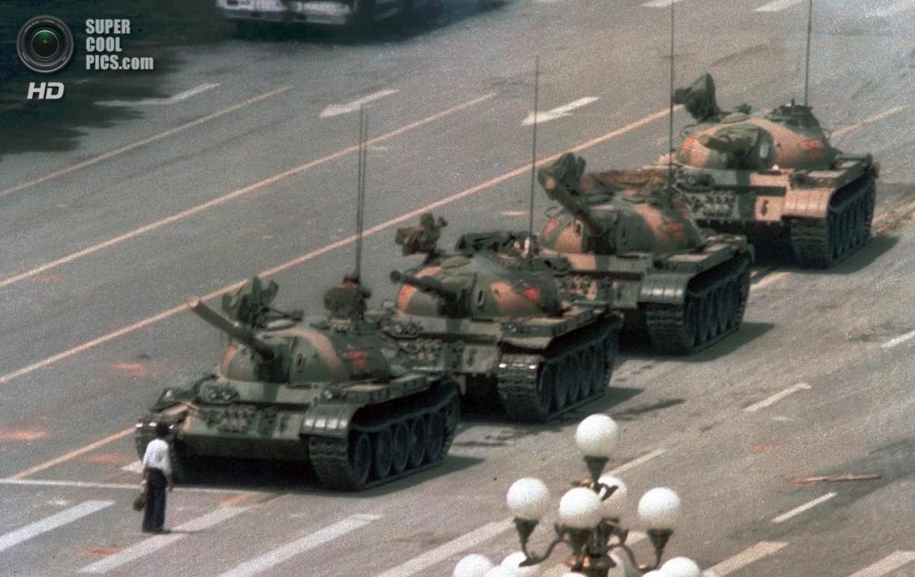 Китай. Пекин. 5 июня 1989 года. «Неизвестный бунтарь» — мужчина, ставший символом событий на площади Тяньаньмэнь. В течение получаса он в одиночку сдерживал колонну танков. Вскоре его увели, а танки продолжили свой путь по бульвару Сиань. (AP Photo/Jeff Widener)