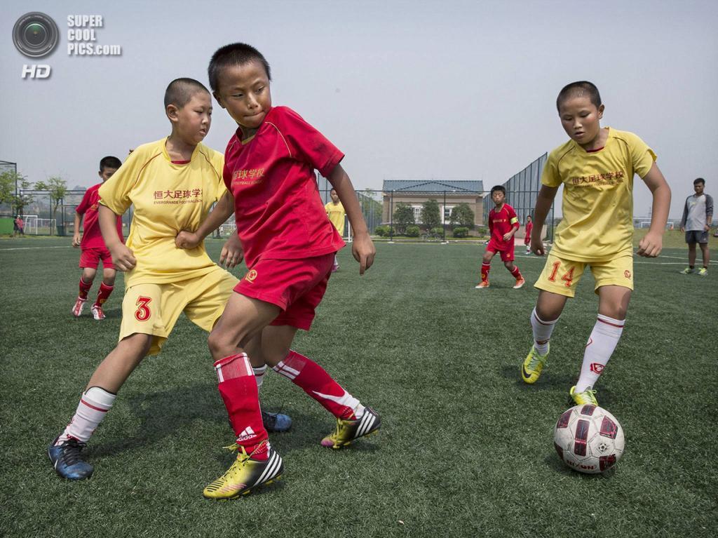 Китай. Цинъюань, Гуандун. 13 июня. Спарринг в футбольной школе «Эвергранде». (Kevin Frayer/Getty Images)