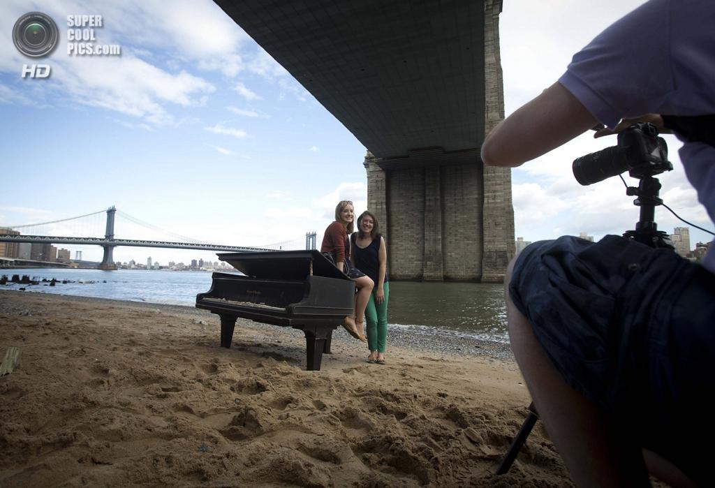 США. Нью-Йорк. 31 мая. Прохожие фотографируются у старого рояля под Бруклинским мостом. (REUTERS/Carlo Allegri)