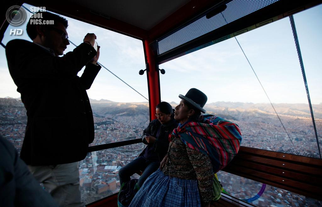 Боливия. Ла-Пас. 2 июня. Мужчина делает снимок женщины-аймара в кабинке канатной дороги. (AP Photo/Juan Karita)