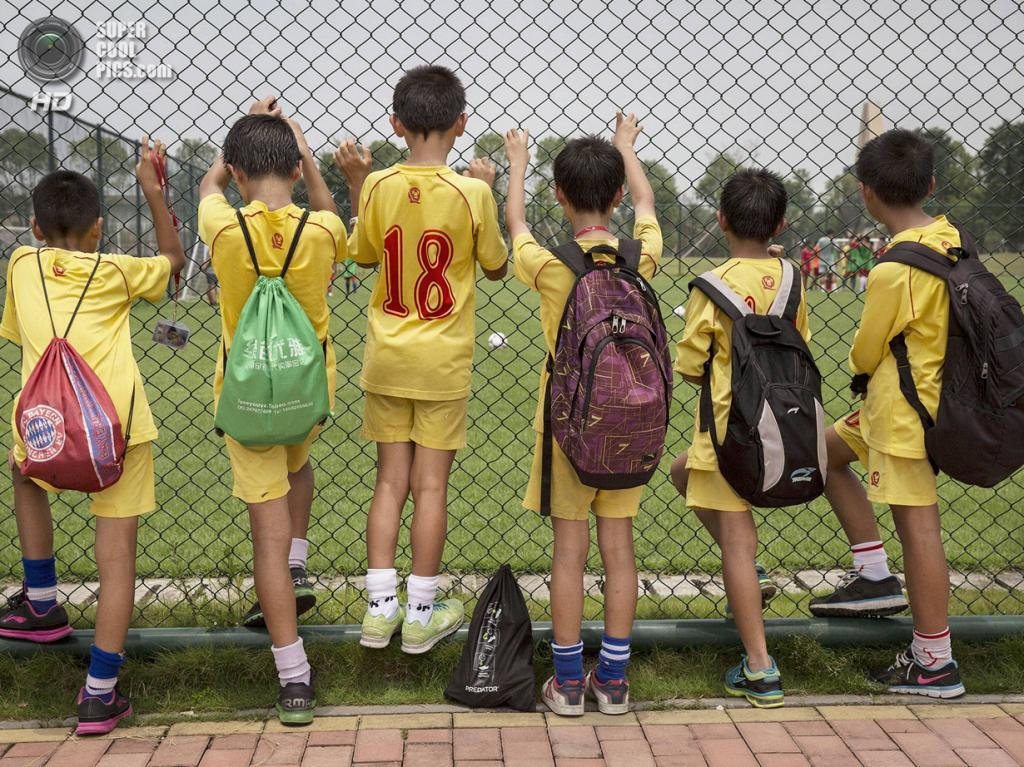 Китай. Цинъюань, Гуандун. 13 июня. Мальчишки наблюдают за тренировкой своих товарищей. (Kevin Frayer/Getty Images)