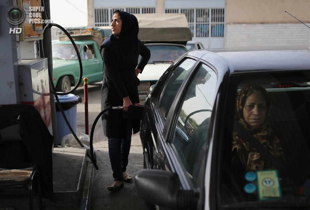 Иран. Шахиншехр, Исфахан. 3 июня. Работница заправки обслуживает клиента. (John Moore/Getty Images)