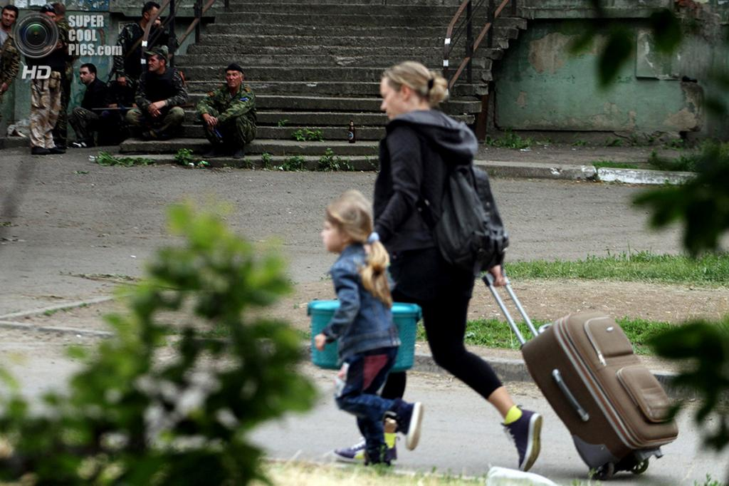 Украина. Луганск. 2 июня. Женщина с ребёнком и чемоданом на фоне вооружённых активистов Луганской народной республики. (STR/AFP/Getty Images)
