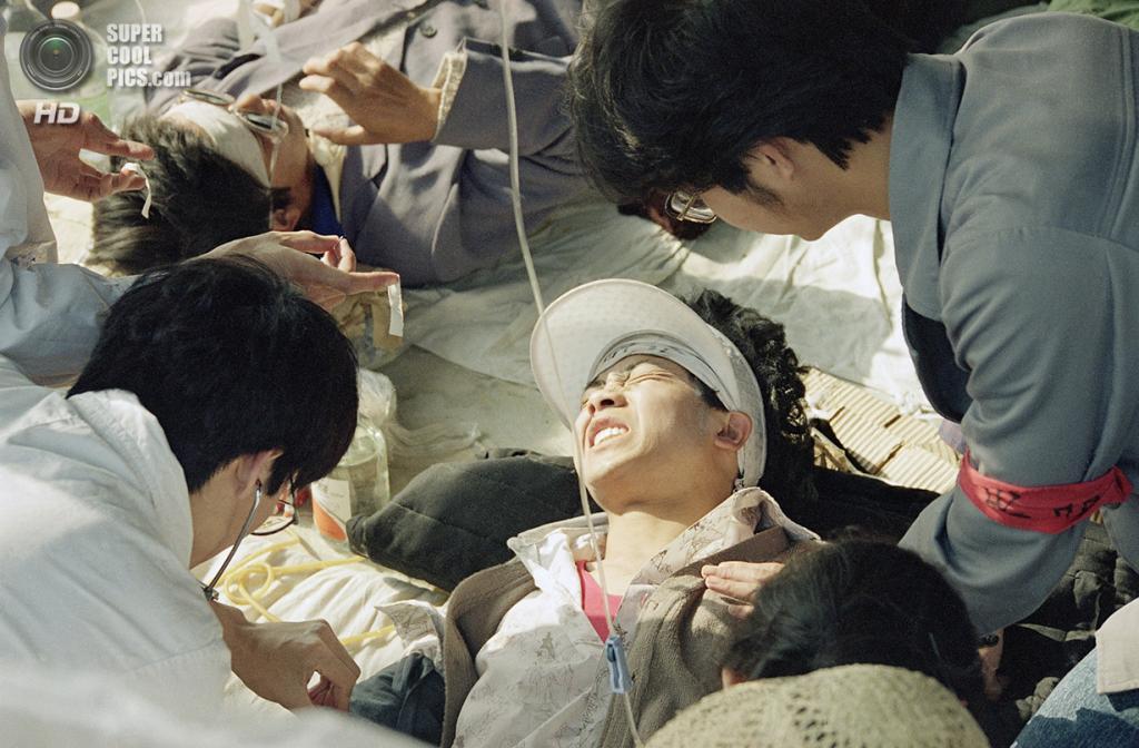 Китай. Пекин. 17 мая 1989 года. Медики оказывают первую помощь студенту, участвующему в голодовке. (AP Photo/Sadayuki Mikami)