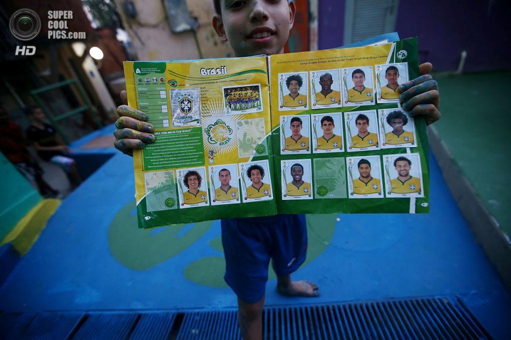 Бразилия. Рио-де-Жанейро. 7 июня. Мальчик демонстрирует коллекцию стикеров с игроками сборной Бразилии. (Mario Tama/Getty Images)