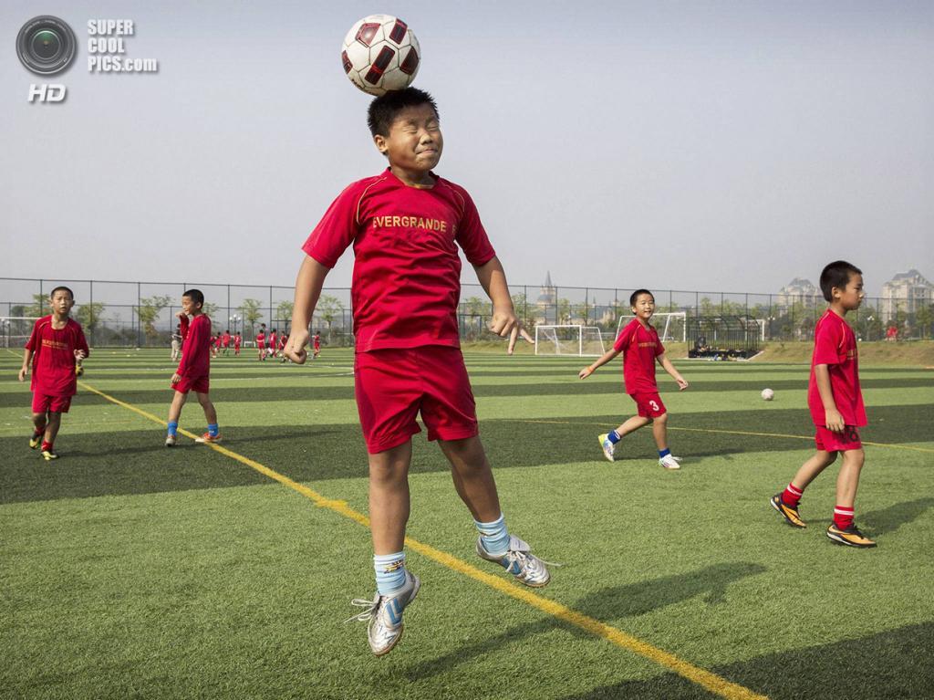 Китай. Цинъюань, Гуандун. 13 июня. Тренировка игры головой. (Kevin Frayer/Getty Images)