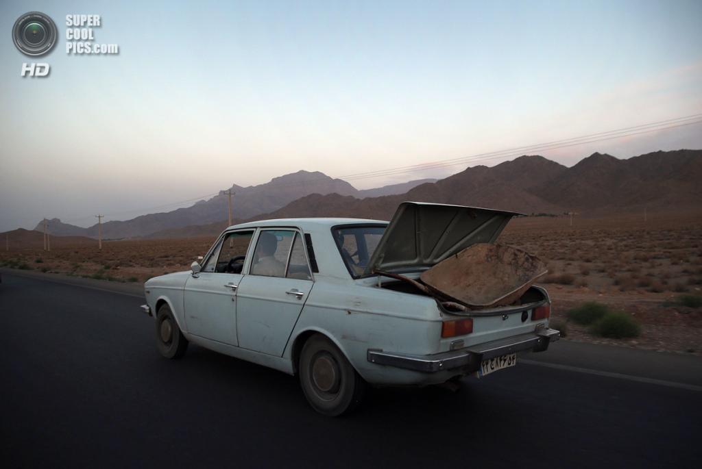 Иран. Несрабад, Исфахан. 30 мая. Автомобиль мчит по шоссе с тачкой в багажнике. (John Moore/Getty Images)