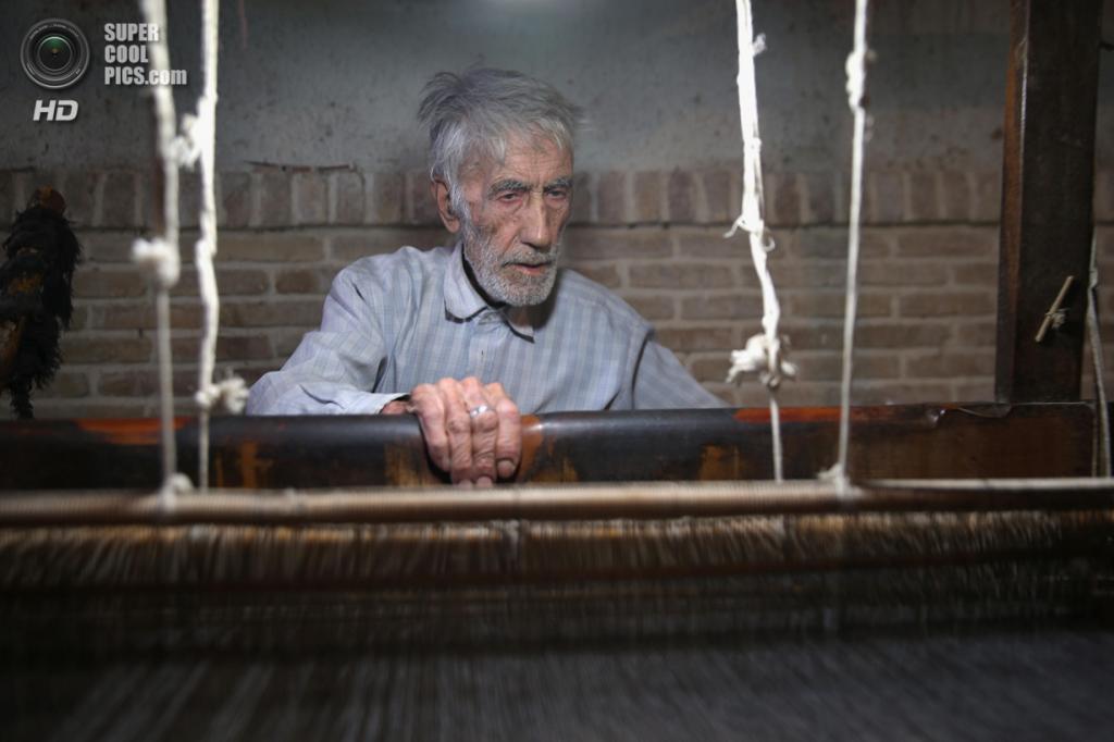 Иран. Мейбод, Йезд. 1 июня. 83-летний ткач Али Гаюми делает ткань из верблюжьей шерсти на своём станке. Гаюми работает в одной и той же подземной мастерской с 10 лет. Он один из немногих, кто всё ещё делает это вручную. Мейбод был обязательной остановкой на торговых путях со времён Государства Сасанидов. (John Moore/Getty Images)