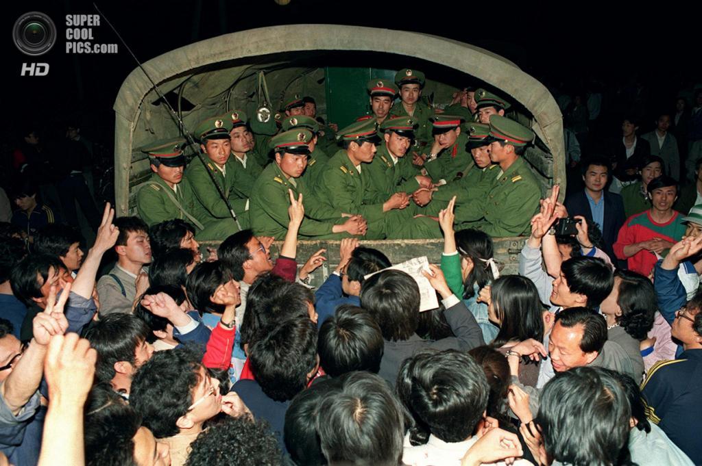 Китай. Пекин. 20 мая 1989 года. Грузовик с солдатами в окружении студентов, демонстрирующих «викторию» — жест мира. (Catherine Henriette/AFP/Getty Images)