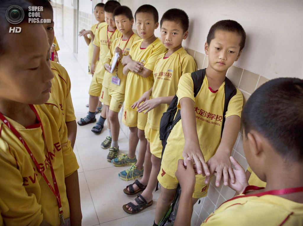 Китай. Цинъюань, Гуандун. 13 июня. В ожидании перед столовой. (Kevin Frayer/Getty Images)
