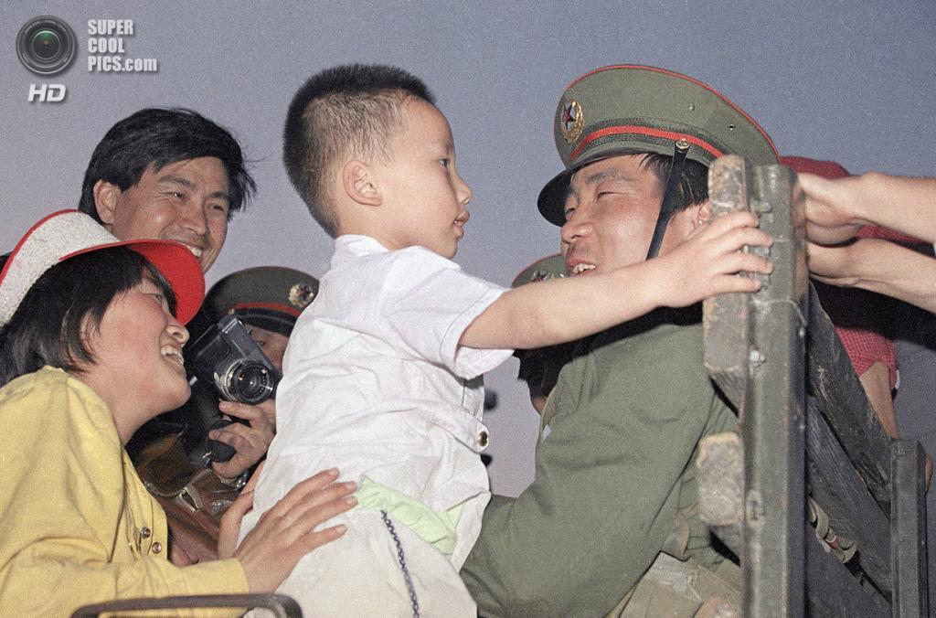 Китай. Пекин. 20 мая 1989 года. Женщина знакомит солдата со своим сыном в 8 км от площади Тяньаньмэнь, где их остановили простые прохожие. (Catherine Henriette/AFP/Getty Images)