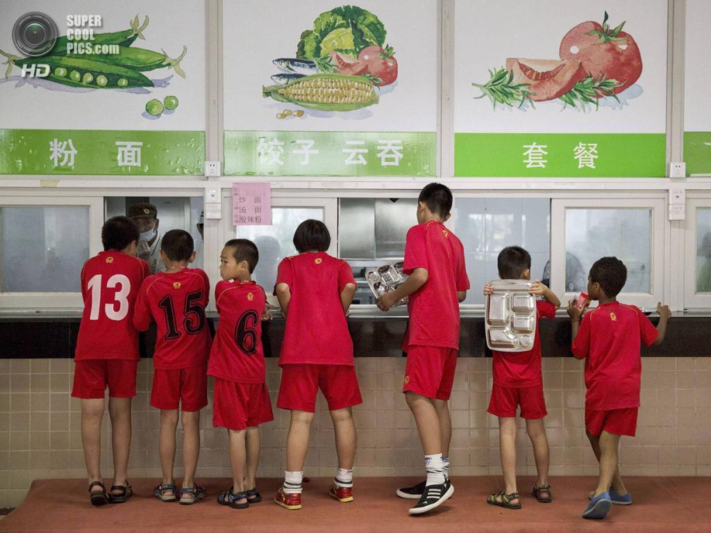 Китай. Цинъюань, Гуандун. 13 июня. Ребята получают свой паёк. (Kevin Frayer/Getty Images)