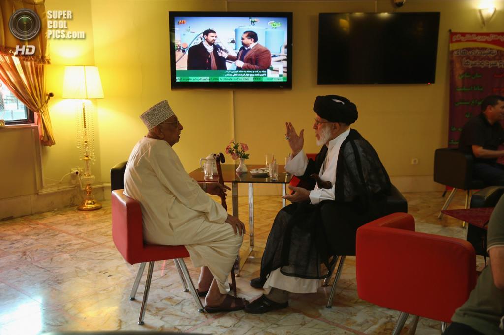 Иран. Кум. 3 июня. Пожилые мусульмане беседуют в кофейне при отеле перед походом в мечеть. (John Moore/Getty Images)