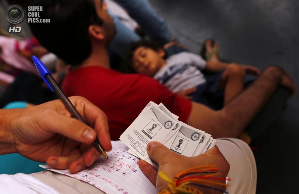Бразилия. Сан-Паулу. 8 июня. Мужчина отмечает номера стикеров, которые у него уже есть. (REUTERS/Kai Pfaffenbach)
