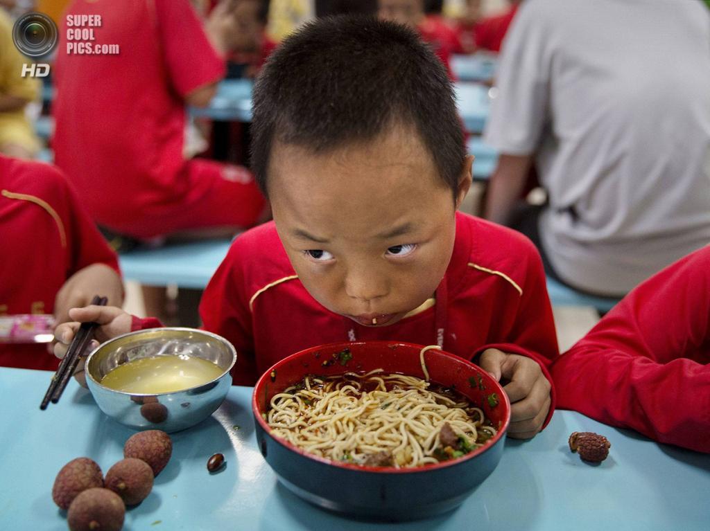 Китай. Цинъюань, Гуандун. 13 июня. Что-то не очень похоже на среднестатистическую диету футболиста. (Kevin Frayer/Getty Images)