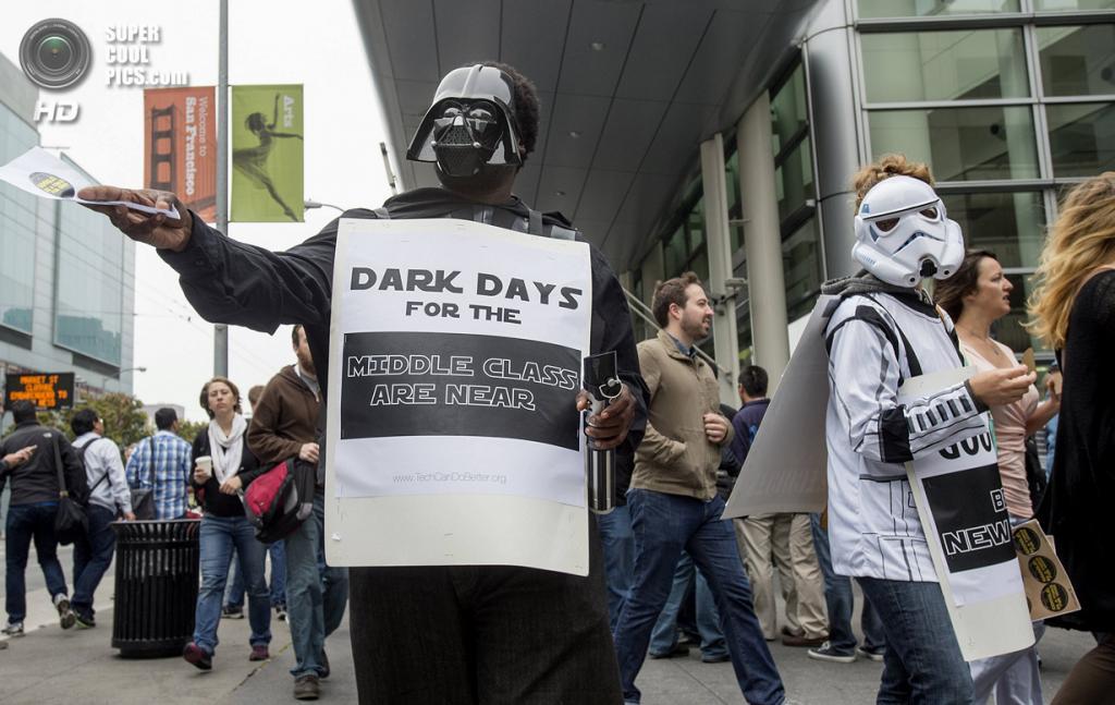 США. Сан-Франциско, Калифорния. 25 июня. «Надвигаются тёмные дни для среднего класса», — гласит плакат Брюса Миллера-Уильямса, вышедшего на протест под сводами «Москоне-центра» в костюме Дарта Вейдера. (REUTERS/Noah Berger)