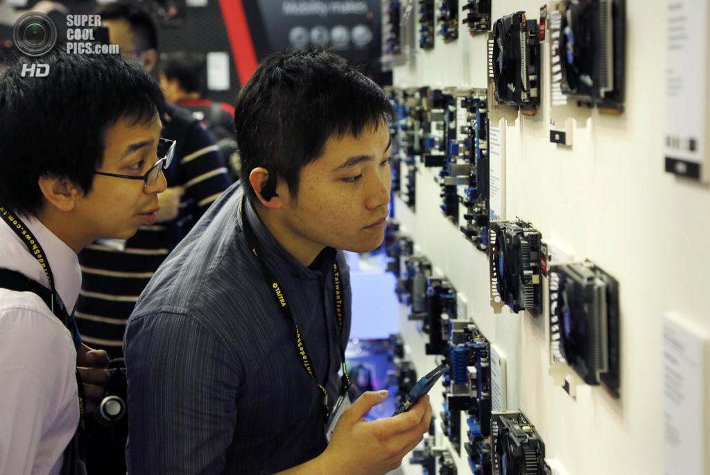 Тайвань. Тайбэй. 3 июня. Посетители рассматривают системы охлаждения. (AP Photo/Wally Santana)