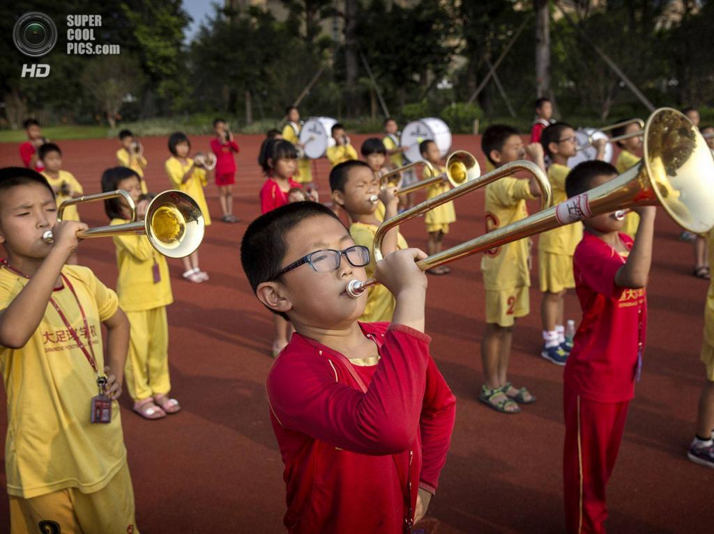 Китай. Цинъюань, Гуандун. 13 июня. Школьный оркестр. (Kevin Frayer/Getty Images)