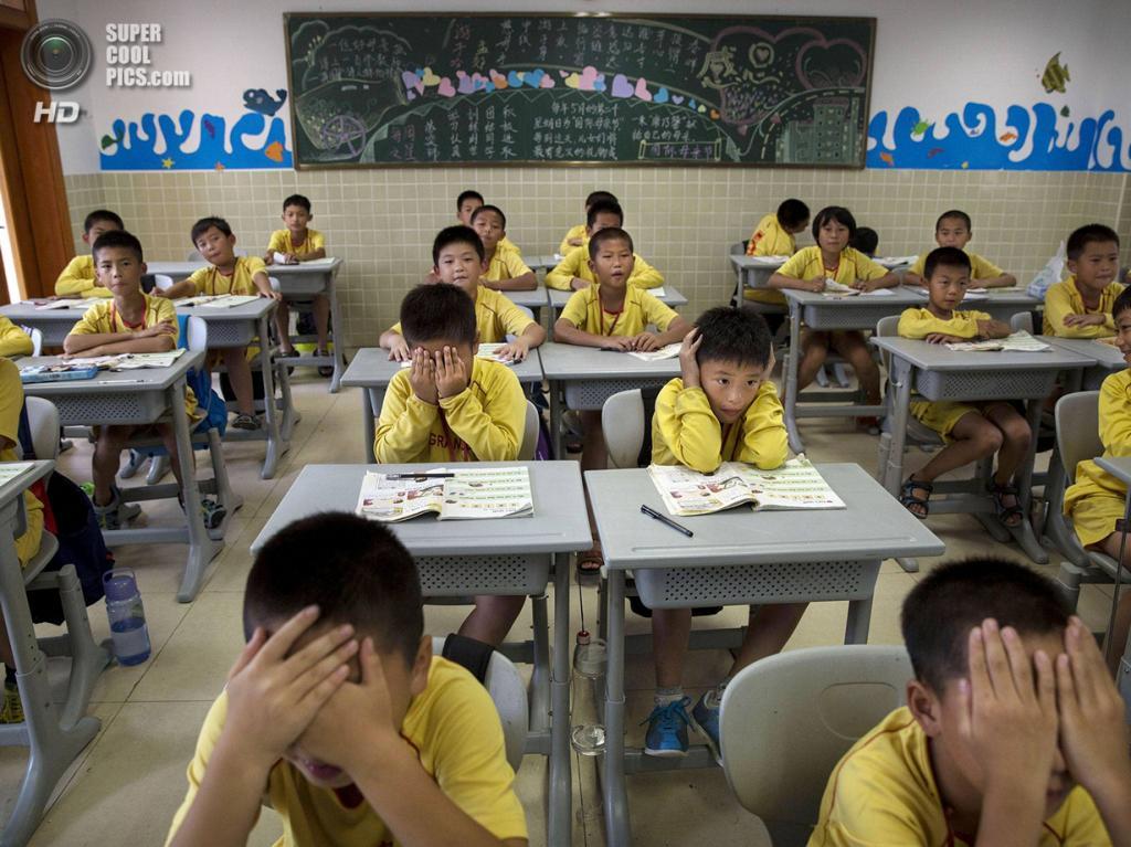 Китай. Цинъюань, Гуандун. 13 июня. Вряд ли это разбор тактических схем — обыкновенные школьные занятия. (Kevin Frayer/Getty Images)