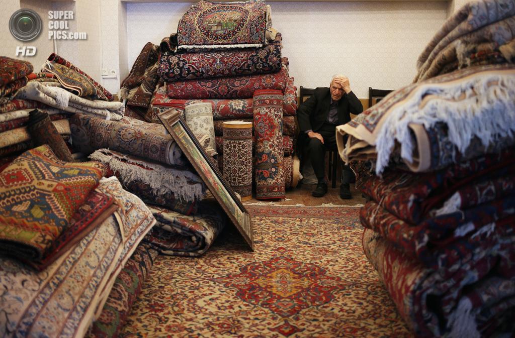 Иран. Исфахан. 2 июня. Продавец ковров в ожидании покупателей на базаре. Иранская ковровая промышленность, некогда самая большая в мире, очень сильно пострадала от международных санкций. (John Moore/Getty Images)