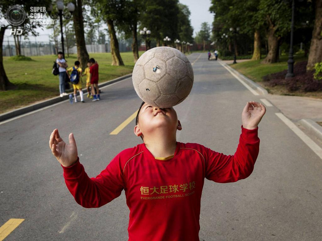 Китай. Цинъюань, Гуандун. 13 июня. Юный китайский футболист демонстрирует свои умения. (Kevin Frayer/Getty Images)