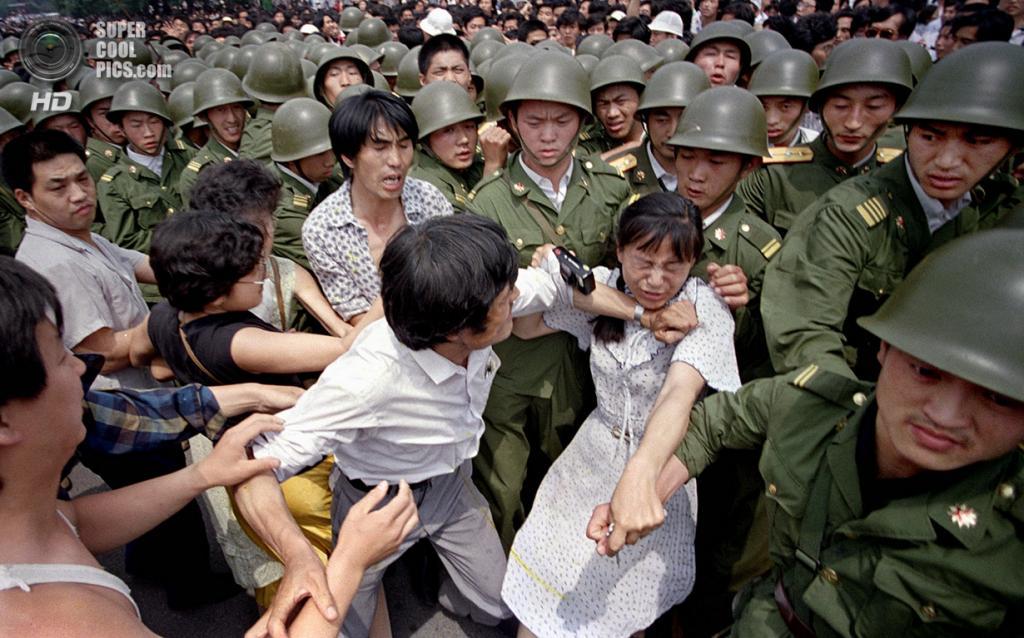Китай. Пекин. 3 июня 1989 года. Женщина с фотоаппаратом, зажатая между солдатами и демонстрантами. (AP Photo/Jeff Widener)