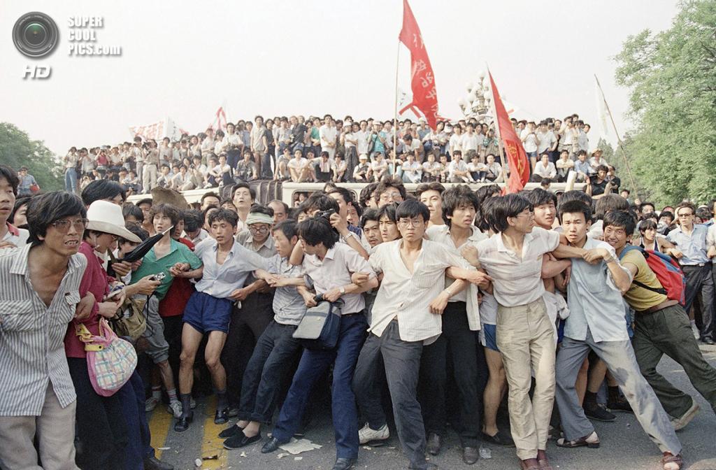 Китай. Пекин. 3 июня 1989 года. Студенты пытаются сдержать агрессивно настроенную толпу от погони за отступающими солдатами. Люди были разозлены попытками правительства разогнать толпу при помощи слезоточивого газа и дубинок. (AP Photo/Mark Avary)