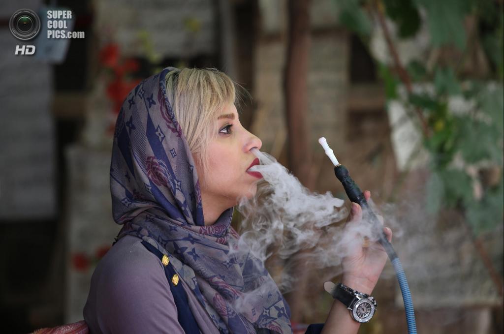 Иран. Шираз, Фарс. 29 мая. Женщина курит кальян во время посещения школы поэзии и каллиграфии. (John Moore/Getty Images)