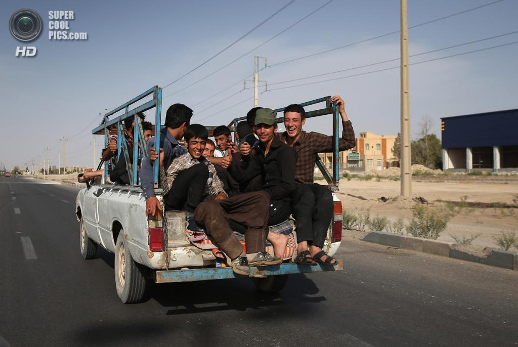 Иран. Эберку, Йезд. 30 мая. Молодые парни едут по городу в кузове пикапа, словно на автобусе. (John Moore/Getty Images)