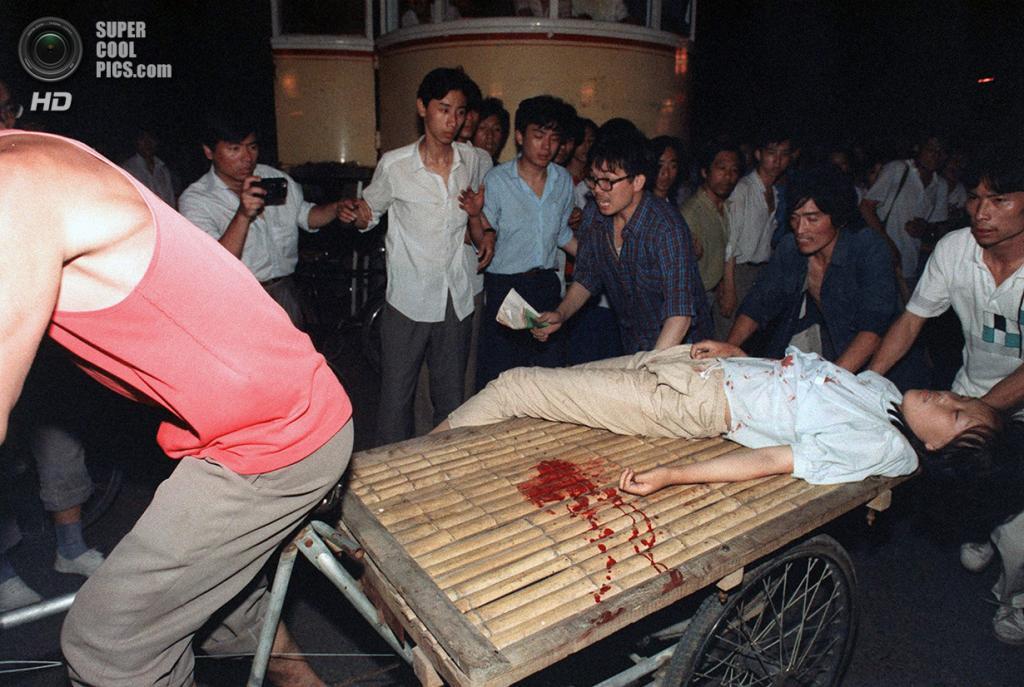 Китай. Пекин. 4 июня 1989 года. Мужчина на велорикше пытается доставить раненую девушку в больницу. (Manuel Ceneta/AFP/Getty Images)