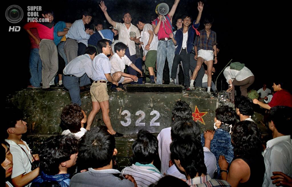 Китай. Пекин. 4 июня 1989 года. Студенты, вооружённые камнями, верхом на правительственном бронетранспортёре. (AP Photo/Jeff Widener)
