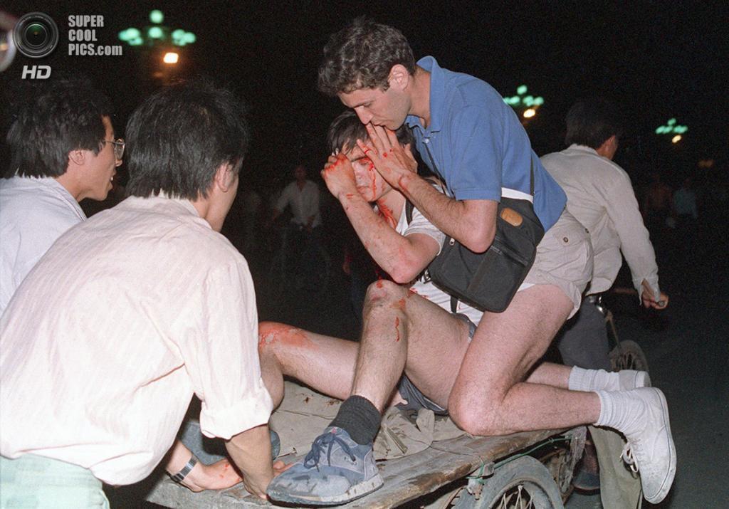 Китай. Пекин. 4 июня 1989 года. Журналист помогает раненому коллеге забраться на велорикшу. (Tommy Cheng/AFP/Getty Images)